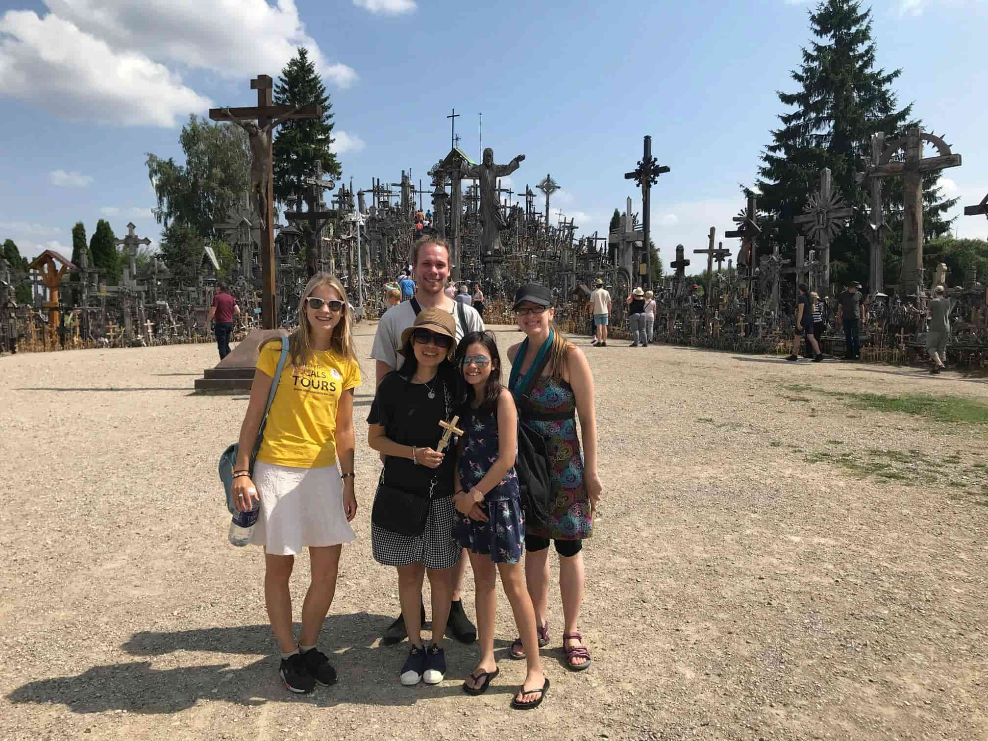 A group of tourists visiting the hill of crosses with Vilnius with Locals Tours guide Milda