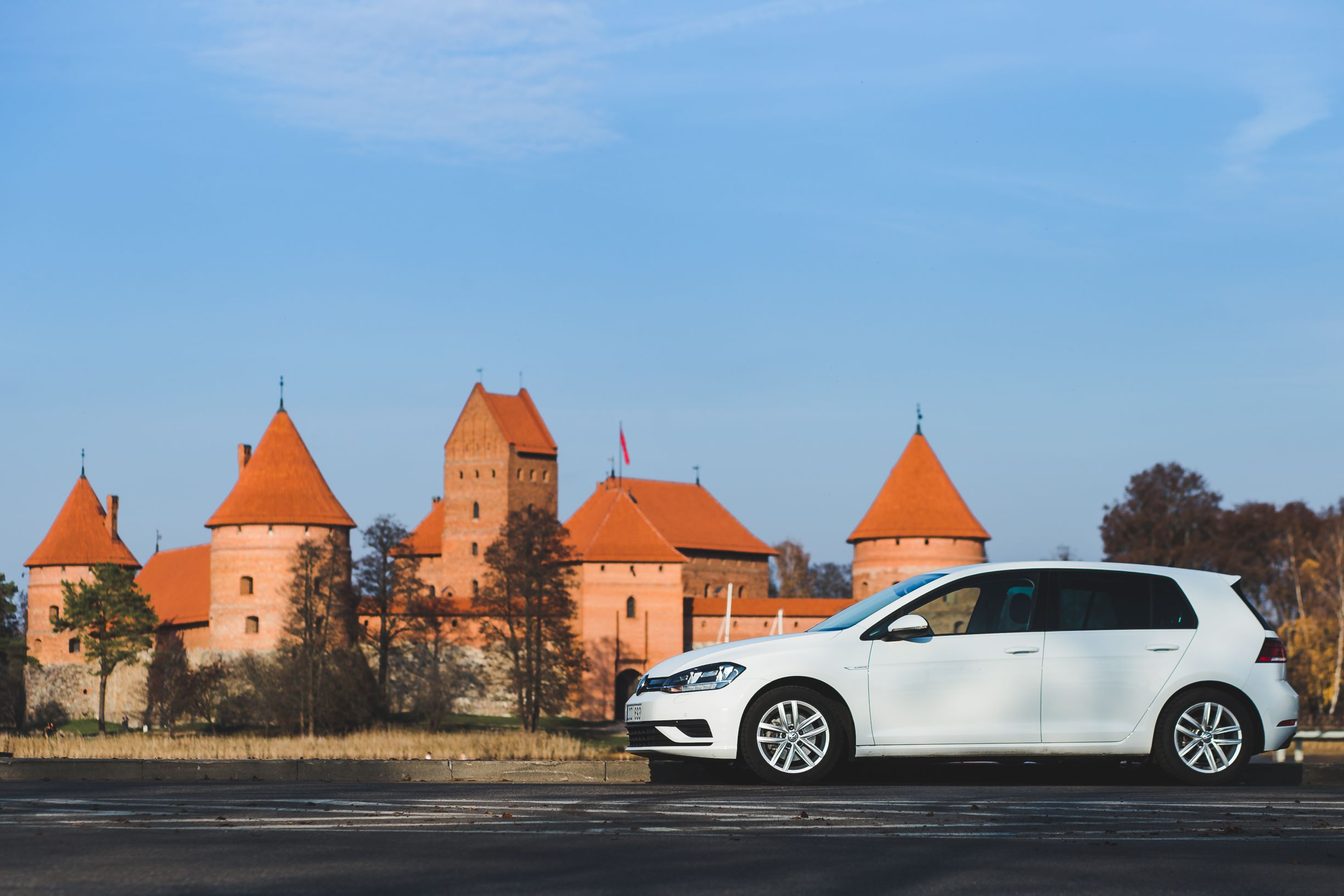 A car from Autocom Car Rental in front of Trakai castle