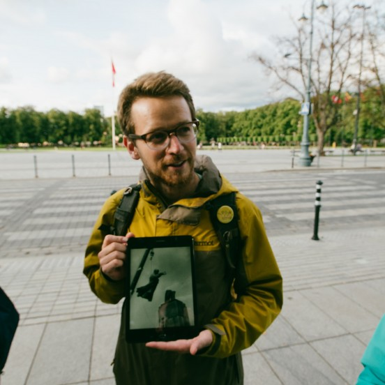 Guide showing picture of Lenin's sculpture on Soviet Vilnius tour